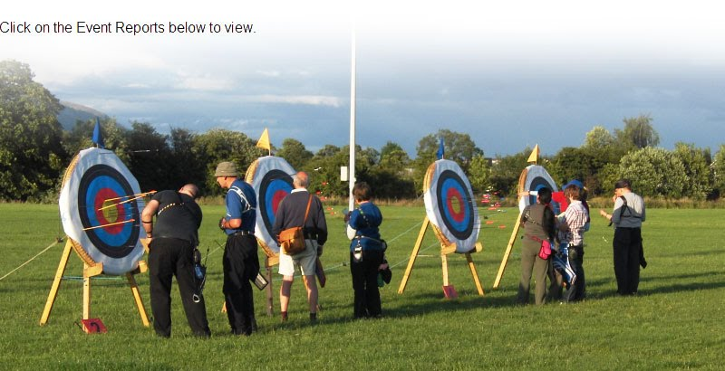 Archers recording scores after completion of an end of shooting during an evening competition event