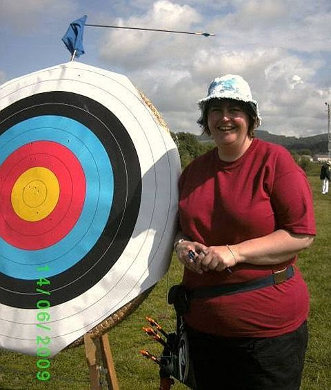 Brenda with another of her infamous trick shots - arrow embedded in target flag above target